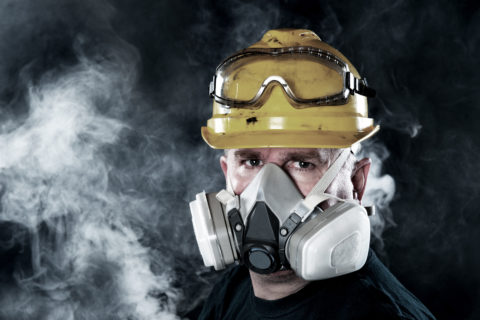 A rescue worker wears a respirator in a smokey, toxic atmosphere.  Image show the importance of protection readiness and safety.